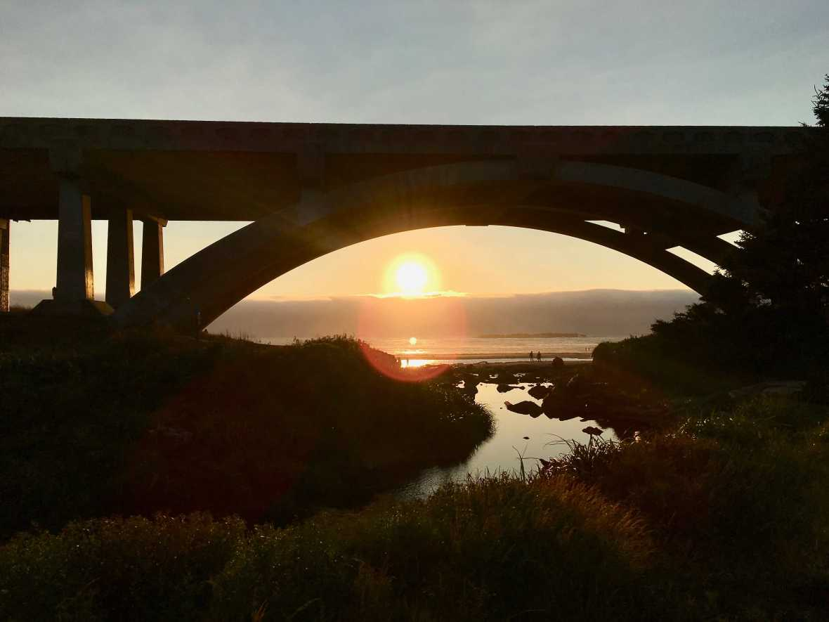 The sun sets under the Spencer Creek Bridge Beverly Beach State Park Oregon sunset