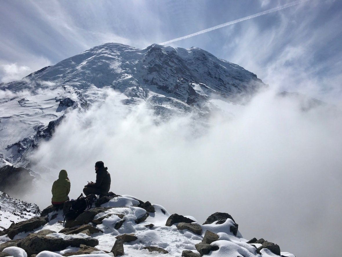 Two people sitting on Third Burroughs Peak in front of Mount Rainier