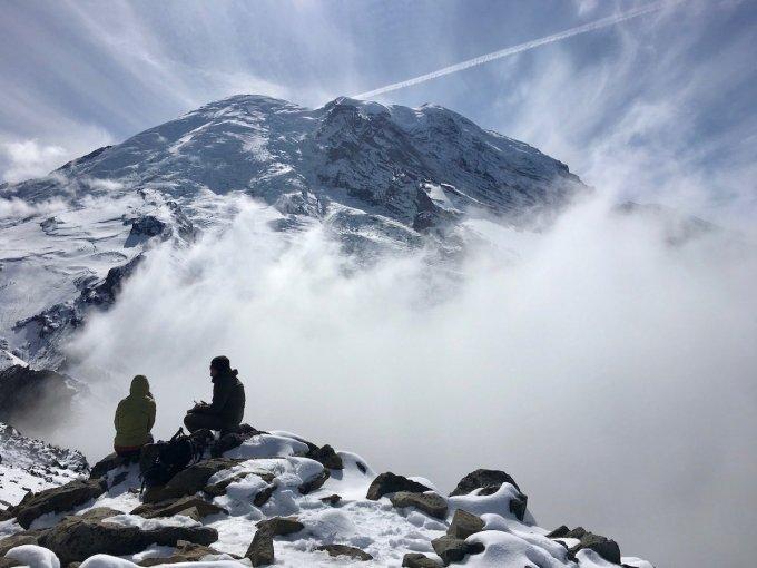 Two people sitting on Third Burroughs Peak in front of Mount Rainier
