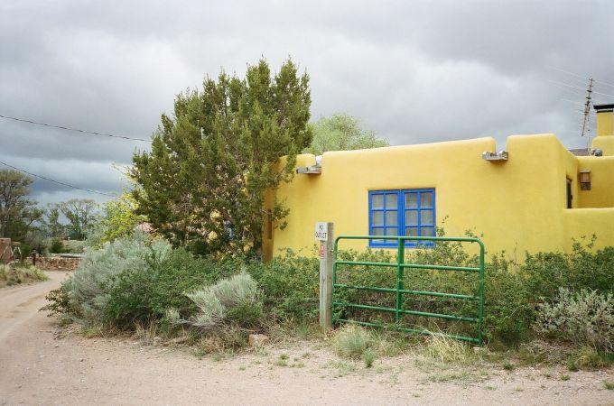 35mm film photograph of Colorful yellow Adobe house in Galisteo, New Mexico