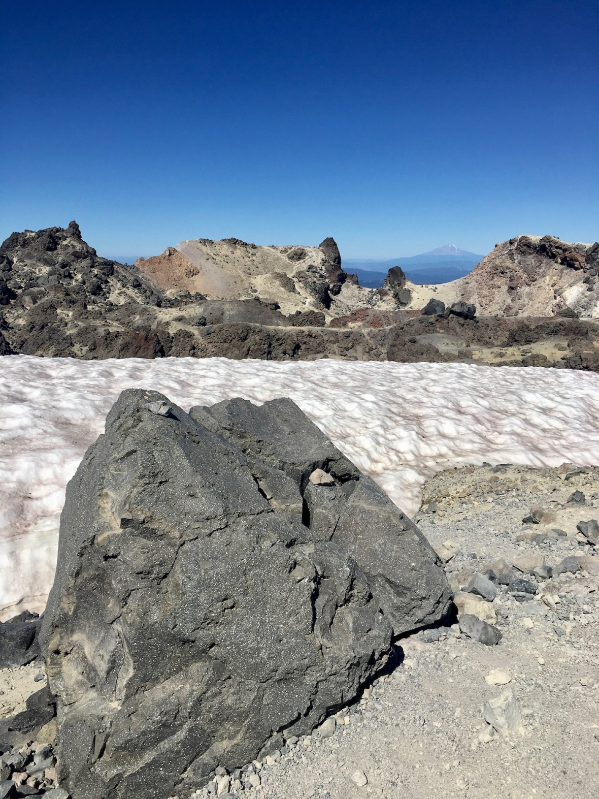 Volcanic boulder, permanent snowfield, caldera rim in Lassen Volcanic National Park
